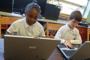 photo of two elementary students with laptops