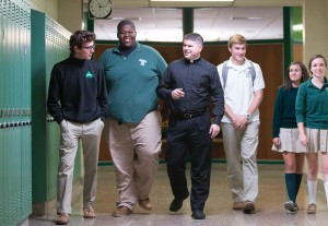 Photo of Dane Connelly walking with students at Bishop Ludden.